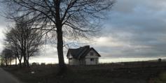 W środku pola nmowy dom. Ohydne