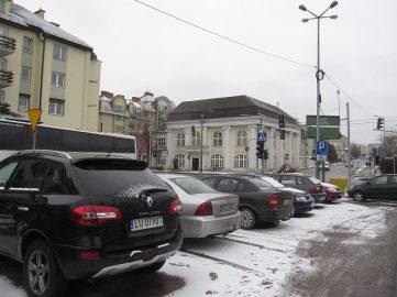 Plac (parking) przed kościołem. Widok na bank