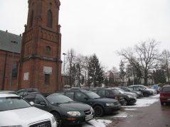 Plac, parking przed kościołem, w tle przedwojenne liceum i dąb wolności posadzony w 1918 roku